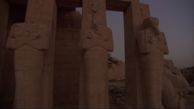 three of four ancient egyptian statues at a ruin site are headless. - decapitated stock videos & royalty-free footage