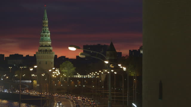 Three of the Kremlin Towers and street lights set against a rich sunset in Moscow, Russia.