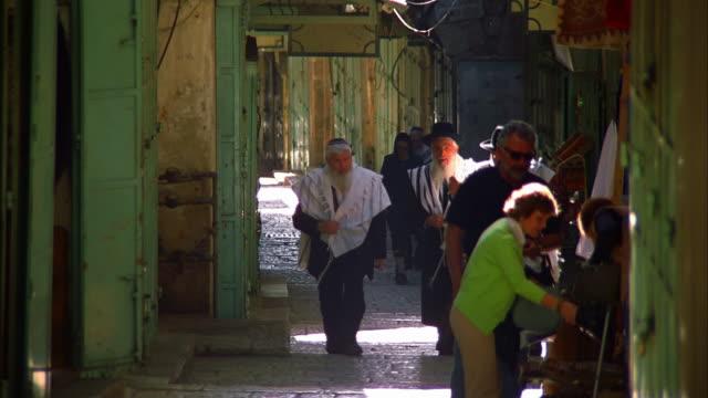 vídeos de stock, filmes e b-roll de ms three orthodox jewish men walking towards camera in narrow street, israel, jerusalem - de braços dados
