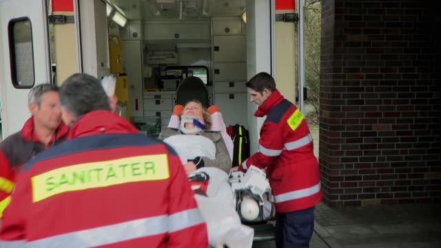 MS, Three paramedics taking patient on hospital gurney out of ambulance, Berlin, Germany