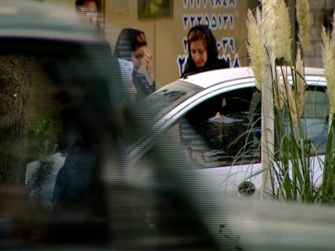 vidéos et rushes de pan three pedestrians entering a taxi from a busy city street / tehran, iran - vêtement religieux