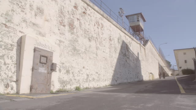 la three pedestrians walking in an empty lot outside prison wall with guard tower and metal door / california, united states - prison guard stock videos and b-roll footage