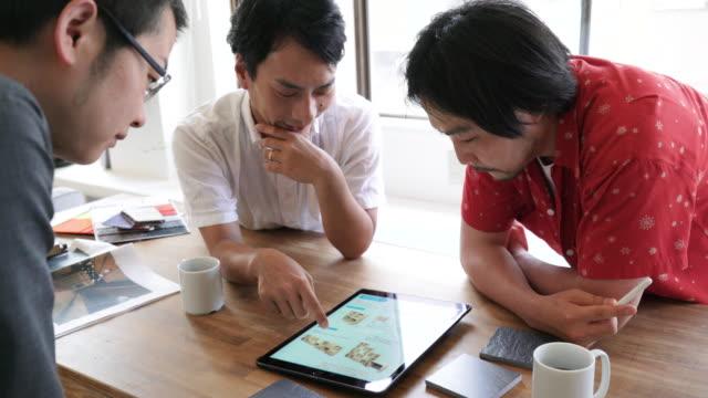 3人の成人男性が材料を選ぶ - タブレット端末点の映像素材/bロール