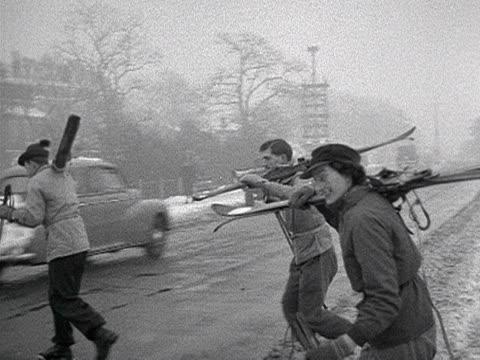 vídeos de stock e filmes b-roll de three people carry skis as they walk to a snowy hampstead heath 1955 - bastão de esqui