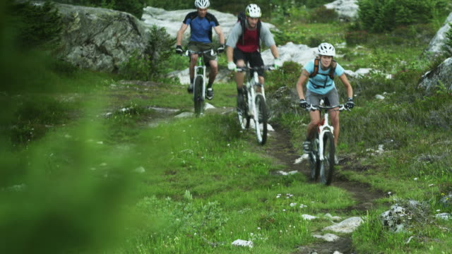 CU TU FOCUSING Three people cycling on mountain trail, Coast Mountains, Squamish, British Columbia, Canada