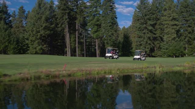 vídeos y material grabado en eventos de stock de three people driving two golf carts on suncadia resort - golf cart