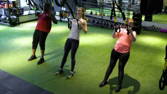 Three people exercising with TRX