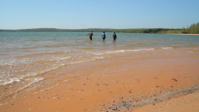 ms pan three people fishing on beach on tiwi islands / northern territory, australia - wiese stock videos & royalty-free footage