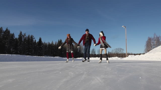 ws ms la pan three people ice skating on outdoor rink / gavle, gastrikland, sweden - ice rink stock videos and b-roll footage