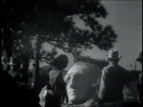 vidéos et rushes de three people observing construction of monument on mount rushmore / face of george washington under construction carved out of mount rushmore - 1931