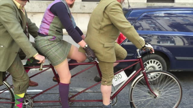three people on a tandem on the the tweed run, passing through london on a glorious spring morning. - arts culture and entertainment stock videos & royalty-free footage