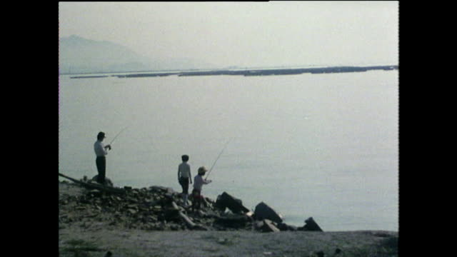 stockvideo's en b-roll-footage met three people  on shore fish in the sea around hiroshima; 1975 - mid volwassen mannen