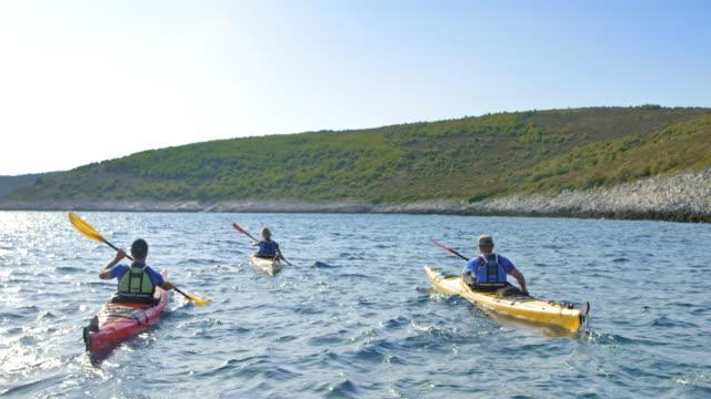 three people paddling their sea kayaks in sunshine - canoeing stock videos & royalty-free footage