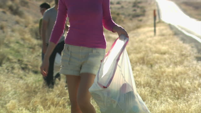three people picking up trash on the side of the road - 20 29 years stock videos & royalty-free footage