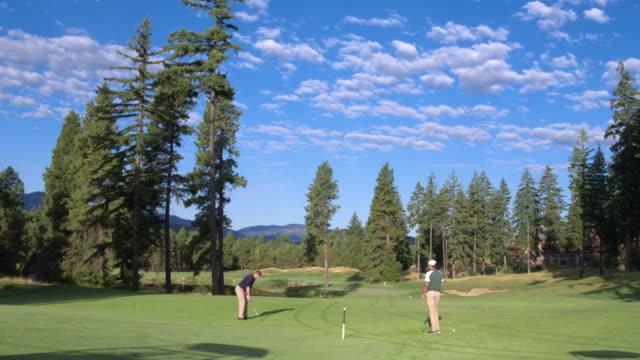 vídeos y material grabado en eventos de stock de three people playing golf by a lake - golf cart