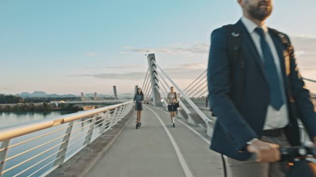 stockvideo's en b-roll-footage met slo mo drie mensen rijden elektrische scooters op de brug - mid volwassen mannen