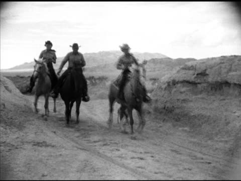 three people riding horses in desert vs desert joshua trees fg w/ mountains bg ws mountains ws men women dressed in western cowboy clothing sitting... - wild west stock videos & royalty-free footage
