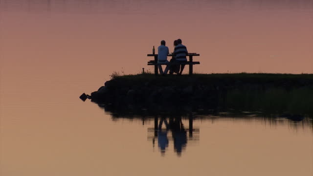 vídeos de stock e filmes b-roll de three people sit at a picnic table at the edge of a beautiful lake in the ekero region of sweden. - mesa de piquenique