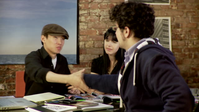 ms, three people sitting at conference table, two men shaking hands, brooklyn, new york city, new york state, usa - schiebermütze stock-videos und b-roll-filmmaterial