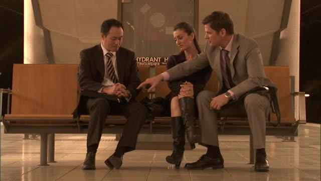 ms, three people sitting on bench, waiting for train on platform, sydney, australia - せっかち点の映像素材/bロール