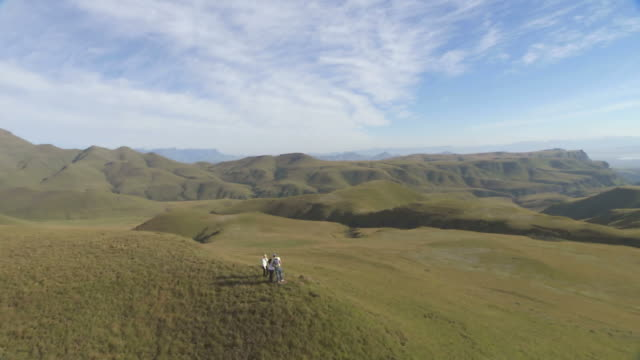 ws aerial ts ds three people standing on grassy hilltop / kwazulu natal, south africa - drakensberg mountain range stock videos & royalty-free footage