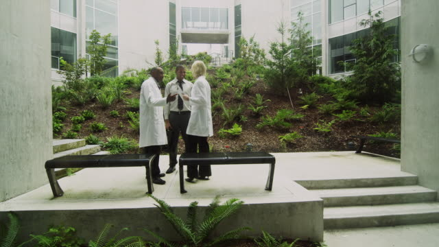 WS Three people talking in courtyard of office building, Squamish, British Columbia, Canada
