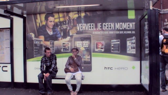 ms three people waiting for trolley at bus stop / amsterdam, netherlands - music poster stock videos & royalty-free footage