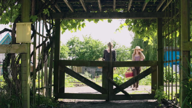 Three people walking out of a garden