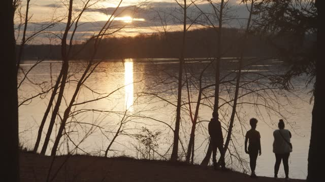three people watch the sun set over the loch raven reservoir on february 27, 2021 in towson, maryland. there have been 546,858 covid-19 deaths in... - three people stock videos & royalty-free footage