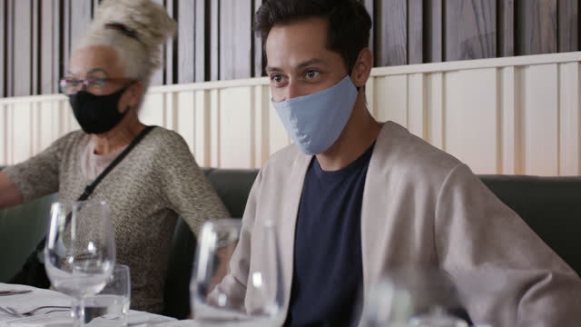 three people wearing face masks sitting down in restaurant - infectious disease stock videos & royalty-free footage