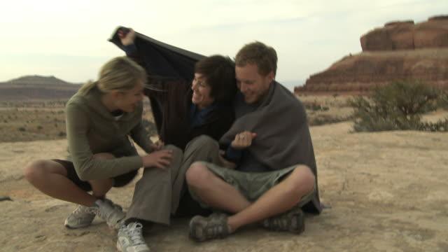 three people wrapping up in a blanket - 男性と複数の女性点の映像素材/bロール