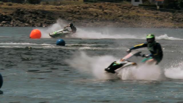 MS SLO MO Three personal watercraft racers around pylons in river / Soap Lake, Washington, United States