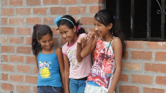 three peruvian girls giggle while leaning against a brick wall with a barred window on the right side - nur kinder stock-videos und b-roll-filmmaterial