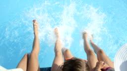 SLOW MOTION CLOSE UP: Three playful women sitting on pool edge splashing water