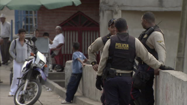 stockvideo's en b-roll-footage met ms selective focus three policemen standing and chatting on petare street / caracas, miranda, venezuela - latijns amerika