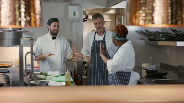 three professional chefs discussing in commercial kitchen - guidance stock videos & royalty-free footage