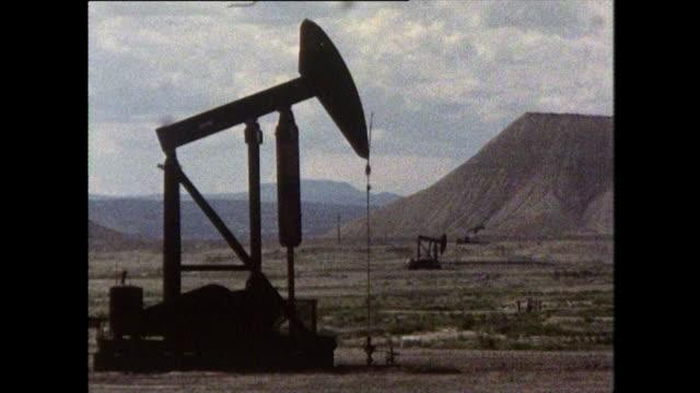 three pumpjacks working in oil field - ölindustrie stock-videos und b-roll-filmmaterial