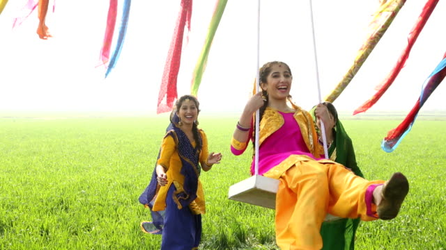 three punjabi young women swinging on rope swing in the farm, punjab, india - punjab india stock videos and b-roll footage