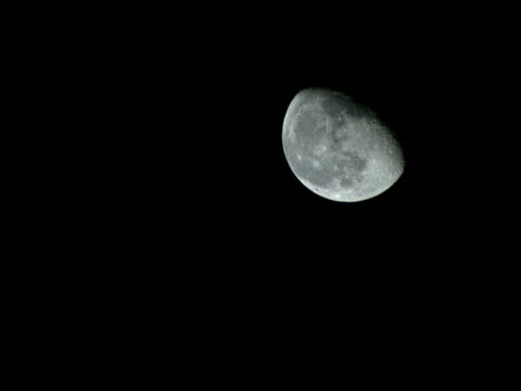 a three quarter moon appears in the black night sky. - weltraum und astronomie stock-videos und b-roll-filmmaterial