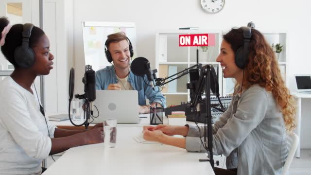 Three Radio Hosts Working in Broadcast Studio