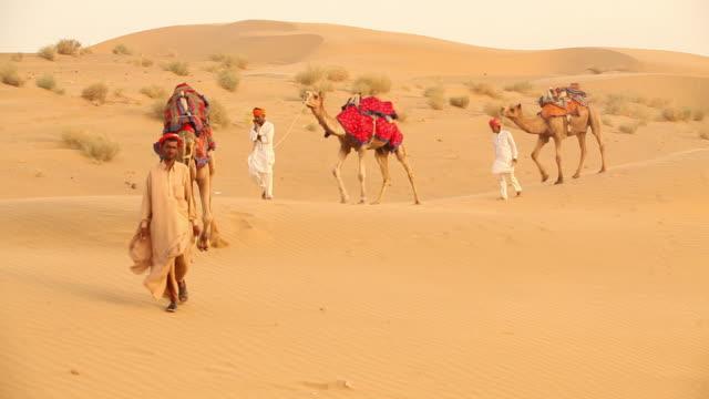 Three rajasthani men walking on desert, Sam Desert, Jaisalmer, Rajasthan, India