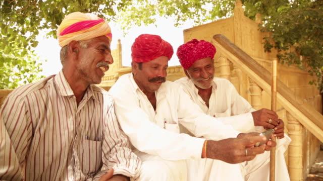 Three rajasthani senior men watching mobile phone, Jaisalmer, Rajasthan, India