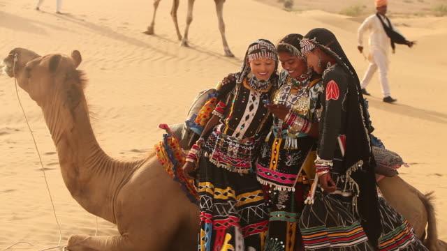 three rajasthani women using a mobile phone, sam desert, jaisalmer, rajasthan, india - arbetsdjur bildbanksvideor och videomaterial från bakom kulisserna