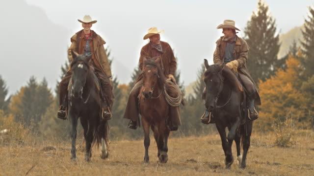 DS tre ranchägare talar och rida sina hästar
