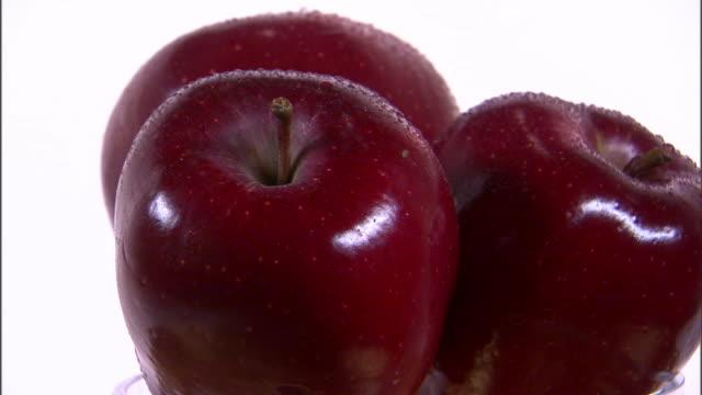vídeos de stock, filmes e b-roll de cu three red apple rotating against white background / orem, utah, usa - enfoque de objeto sobre a mesa