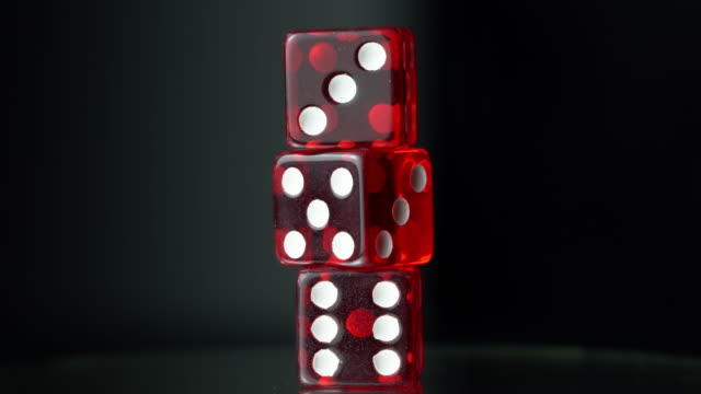 cu three red dices turning rotating on black background - three objects stock videos & royalty-free footage