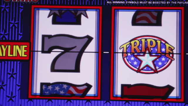 Three reels spin on a gambling slot machine.