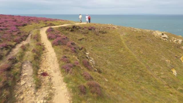 three retired men walking along cliff edge