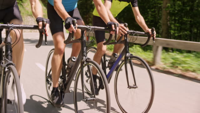 vídeos de stock e filmes b-roll de three road bicycles being ridden by male cyclists in sunshine - ciclo