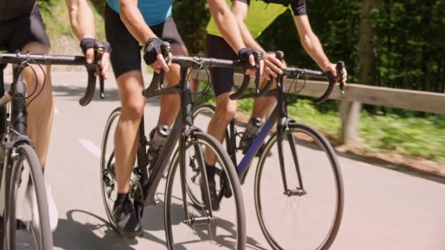 tre väg cyklar rids av manliga cyklister i solsken - landsväg bildbanksvideor och videomaterial från bakom kulisserna